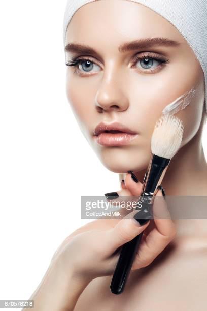 Líneas de crema en la cara de mujer de piel