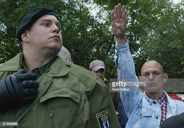 A skinhead gives a Heil Hitler salute before being led away by police September 25 2004 in Berlin Germany Several small groups of skinheads had...