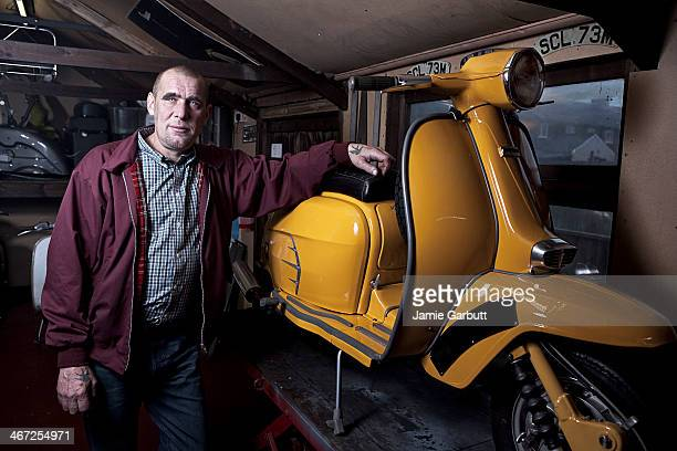 A skinhead in his shed leaning on his scooter