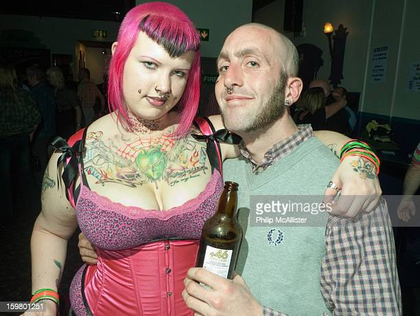 Skinhead scooterist couple pose in a nightclub.They are attending a scooter rally.She is heavily tattooed with pink hair and he is smiling whilst...