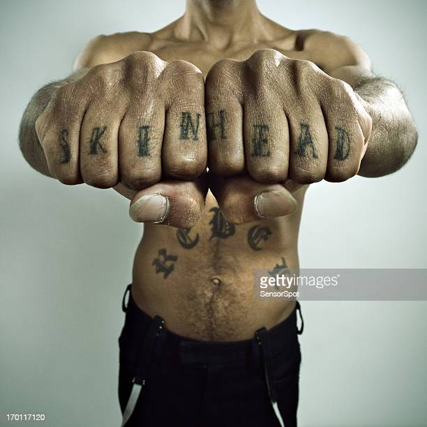 skinhead showing off knuckle tattoo - skinhead stock photos and pictures
