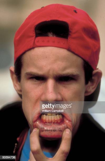 Skinhead youth showing off Skinhead tattoo on inner lip at Ku Klux Klan rally