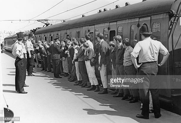 Skinheads arriving at Southend Victoria railway station are lined up to receive advice from police not to get into groups of three or more during...