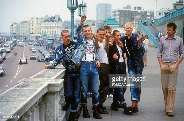 Skinheads gesturing while a pedestrian strolls past Brighton UK 1980's