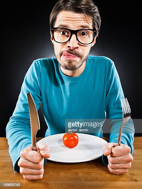 Skinny, hungry man with cherry tomato on plate, humorously