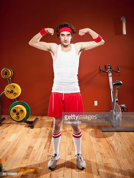 skinny man making muscles at gym
