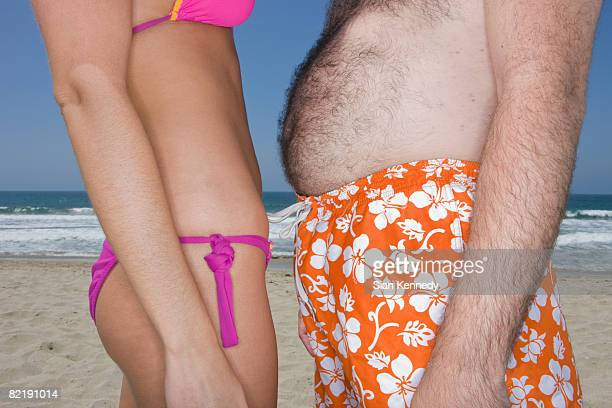 skinny woman and overweight man on the beach - fat man on beach stock photos and pictures
