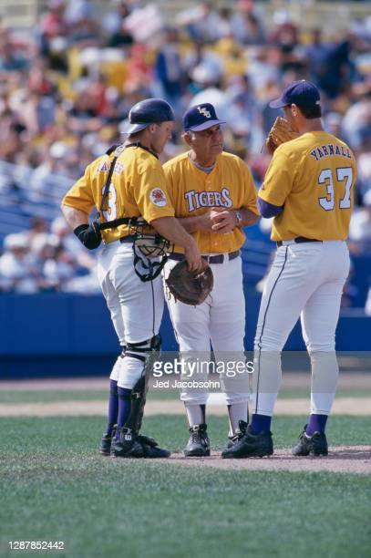 Skip Bertman, Head Coach for the Louisiana State University Tigers talks with pitcher Eddie Yarnall and Catcher Tim Lanier on the mound during the...