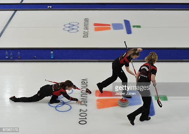 Skip Cheryl Bernard of Canada releases the stone as Cori Bartel and Carolyn Darbyshire brush the ice during the women's curling semifinal game...