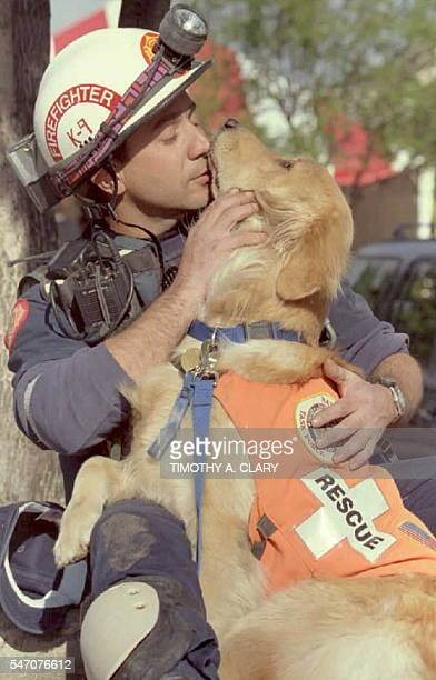 Skip Fernandez of the Dade County Florida Fire Department Search and Rescue Unit gives his dog Aspen a kiss after the two finished their shift...