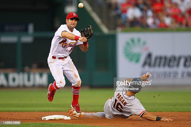 Skip Schumaker of the St Louis Cardinals turns a double play over Angel Pagan of the San Francisco Giants at Busch Stadium on August 7 2012 in St...
