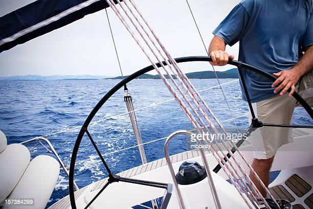 Skipper driving sailboat