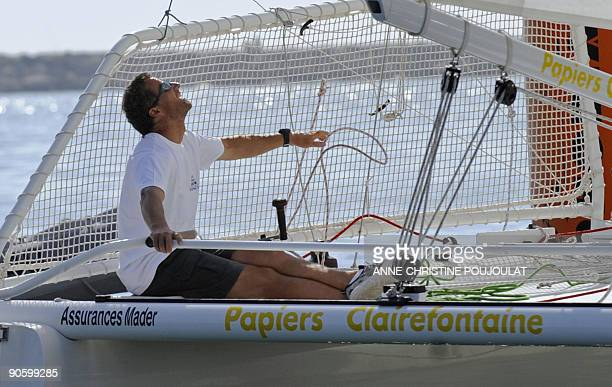 Skipper Michel Desjoyeaux holds the helm on his catamaran during a sailing event on the eve of the launching of the 20th Trophee Clairefontaine...