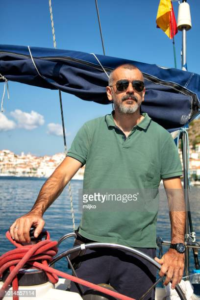 skipper on sailboat - only mid adult men stock pictures, royalty-free photos & images