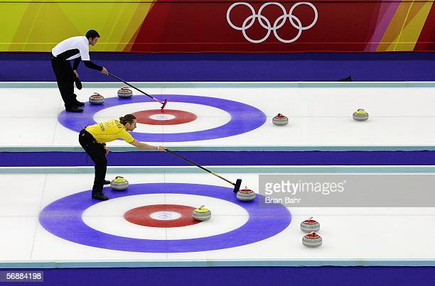 Skipper Sean Becker of New Zealand and skipper Peja Lindholm of Sweden help line up deliveries during a preliminary round of men's curling on Day 9...