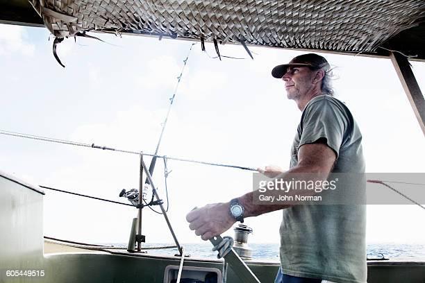 Skipper steering boat with tiller.