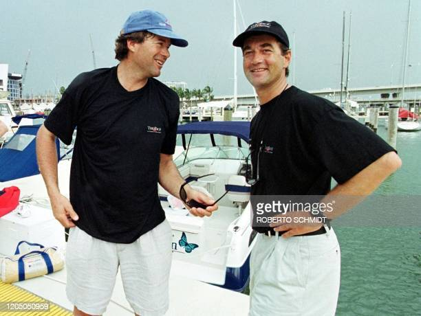 Skippers Bruno Peyron of France Cam Lewis of the US talk before boarding their 86foot Catamaran at a local marina in downtown Miami 30 May 1999...