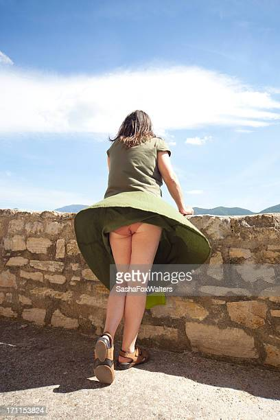 skirt blown by wind - woman bum stock photos and pictures