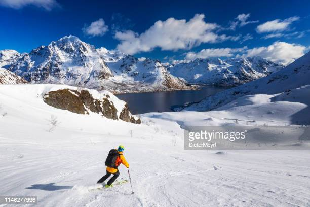 skitouring downhill - powder skiing at  lofoten - norway - nordic skiing event stock pictures, royalty-free photos & images
