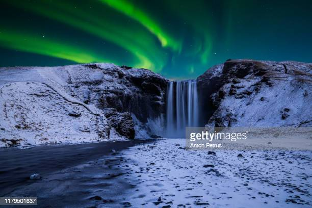 skogafoss waterfall in the winter at night under the northern lights. iceland - iceland stock pictures, royalty-free photos & images