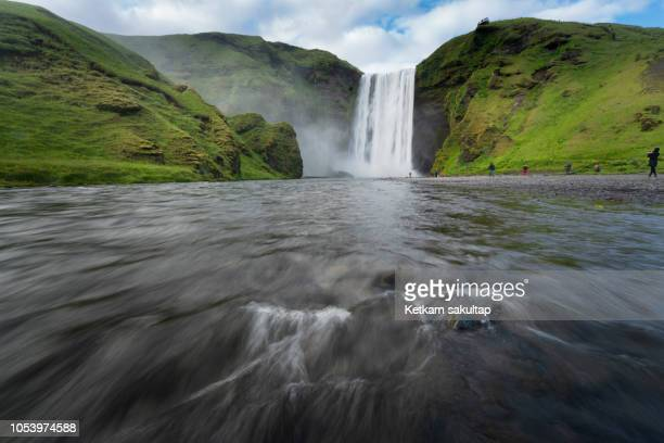 skogafoss waterfall with flowing water in summer. - spring flowing water stock pictures, royalty-free photos & images