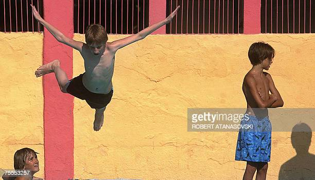 A boy jumps into a swimming pool to cool off in Macedonia's capital Skopje 19 July 2007 The Macedonian government declared a state of emergency as...