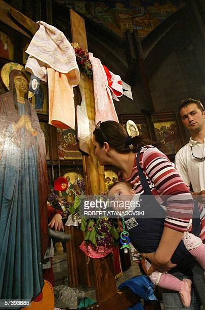 An Orthodox believer with a baby in her arms veneers the Great Crucifix in the Cathedral church Sveti Kliment Ohridski in Skopje during the Good...
