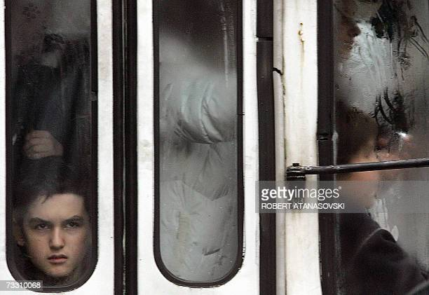 Teenage passengers are seen through the misted doorwindows of an overloaded public bus in the centre of Skopje 13 February 2007 The rainy day filled...