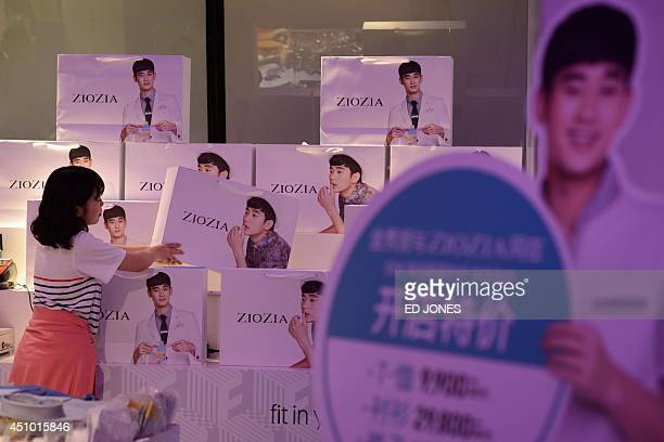 SKoreaentertainmentbusinessTVFEATURE by Jung HaWon In a photo taken on June 12 2014 a shop assistant arranges branded bags displaying the image of an...