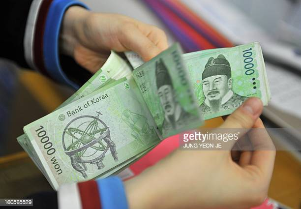 SKoreaJapaneconomytradeforexFOCUS by Jung Hawon This photo taken on February 1 2013 shows a bank employee counting out South Korean won banknotes at...