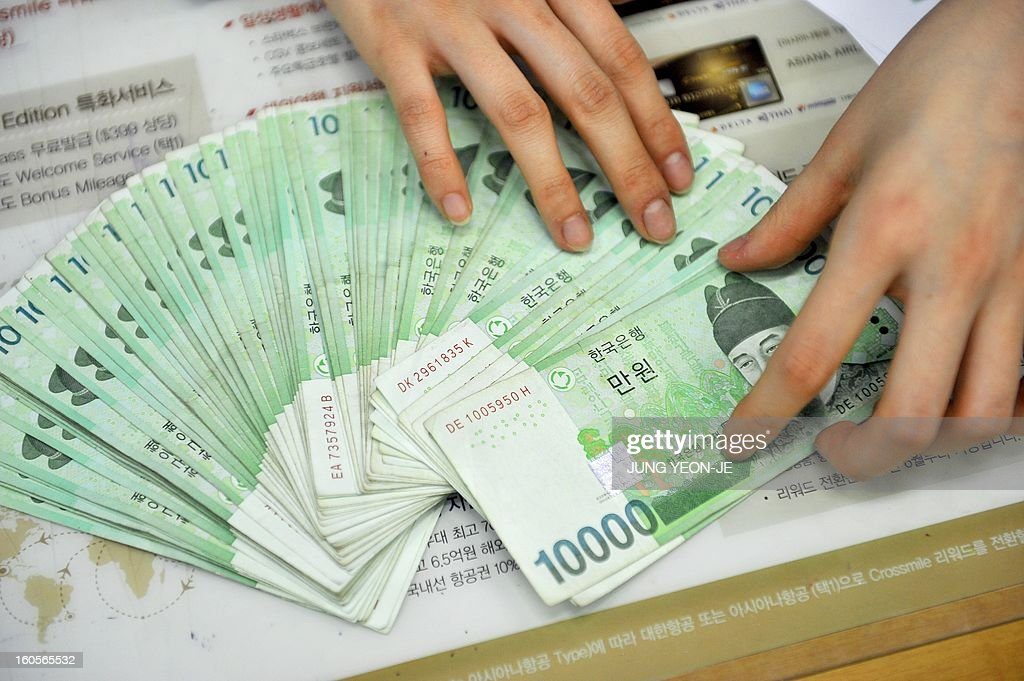 SKorea-Japan-economy-trade-forex,FOCUS by Jung Hawon This photo taken on February 1, 2013 shows a bank employee displaying South Korean won banknotes at the Korea Exchange Bank in Seoul. A surging won and waning yen are eroding the bottom lines of South Korea's export powerhouses who are feeling the pinch after years of gobbling up global market share from their Japanese rivals.