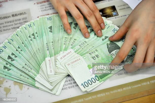 SKoreaJapaneconomytradeforexFOCUS by Jung Hawon This photo taken on February 1 2013 shows a bank employee displaying South Korean won banknotes at...