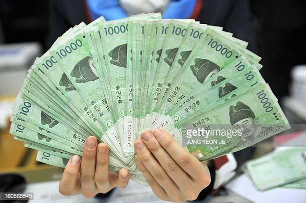 SKoreaJapaneconomytradeforexFOCUS by Jung Hawon This photo taken on February 1 2013 shows a bank employee holding South Korean won banknotes at the...