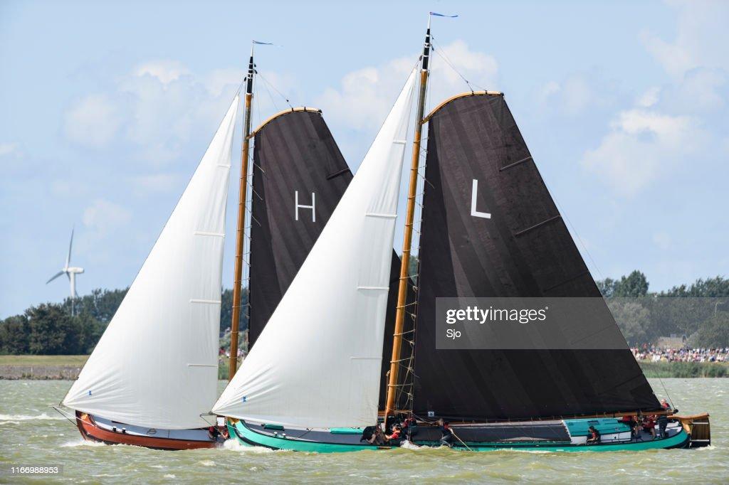 Skûtsje of Heerenveen and Lemmer classic Frisian sailing Tjalk ships during the  2019 annual SKS Skûtsjesilen : Stock Photo