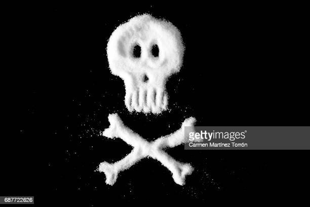 skull and crossbones made of sugar or salt - cholesterol test stock photos and pictures