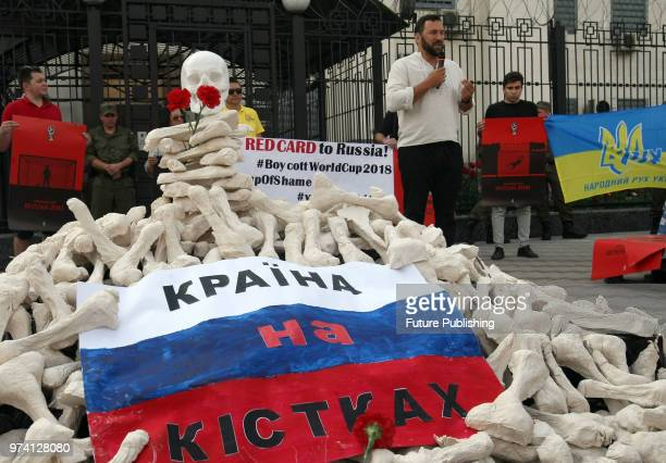 A skull and two red carnations top a pile of papiermache bones during the #Russia The State on the Bones action outside the Embassy of the Russian...