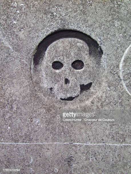 skull engraved and weathered in the stone of an abandoned tomb - capital region stock pictures, royalty-free photos & images