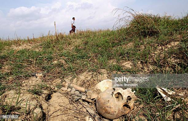 A skull is seen in a shallow makeshift grave along the water on April 27 2009 in the Irrawady delta village of Tha Ma Thukha Myanmar A year after the...