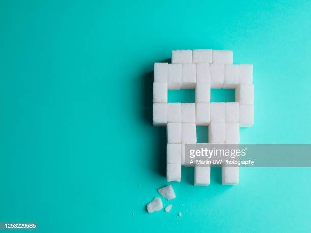 skull made of sugar cubes with a broken tooth. concept of tooth decay. - zucker stock-fotos und bilder