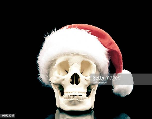 skull wearing a santa hat on a black background. - christmas background stock photos and pictures