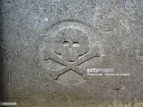 skull with crossbones engraved and patinated in the stone of an abandoned tomb - capital region stock pictures, royalty-free photos & images