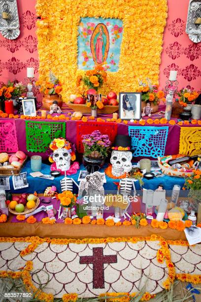 Skulls and skeletons photos of the departed flowers and a virgin mary on a public altar at the El Campo Santoscemetry on Dia de los Muertos the Day...