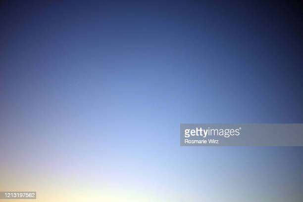sky above: color gradient from light yellow to deep blue - donkerblauw stockfoto's en -beelden