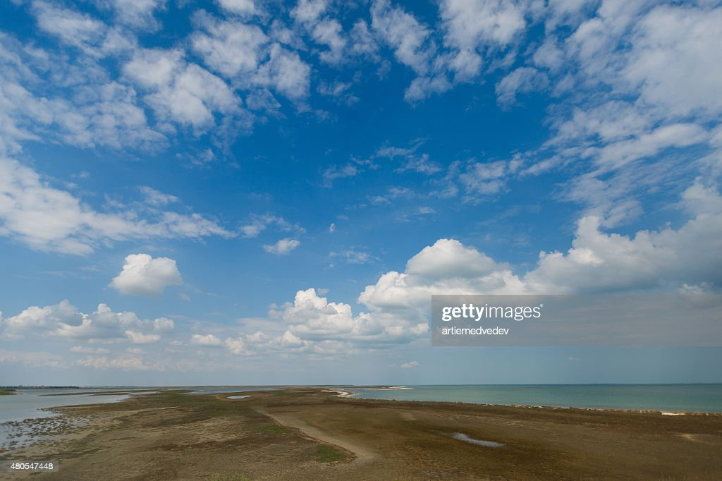 Sky and big clouds over firth with horizon line : Stock Photo