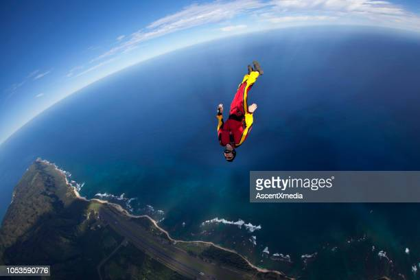 sky diver falls through lofty skies - exhilaration stock pictures, royalty-free photos & images