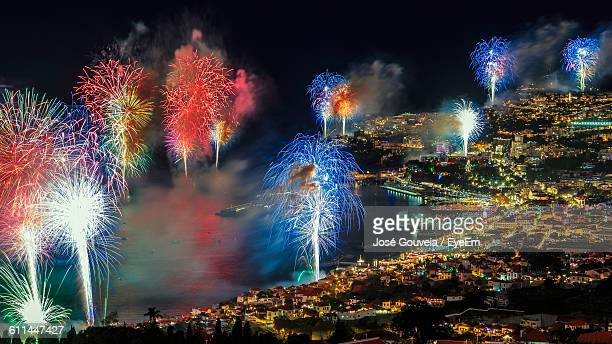 sky illumed with fire crackers over town - funchal stock pictures, royalty-free photos & images