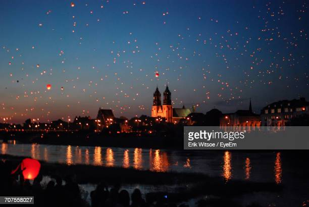 Sky Lanterns Flying Over River By City During Dusk