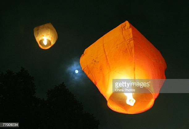 Sky lanterns or Kongming Lantern are flied at a community to mark the MidAutumn Festival on September 25 2007 in Shenzhen of Guangdong Province China...