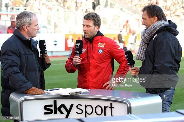 Sky moderator Heiko Mallwitz speaks with head coach Rico Schmitt of Aue and head coach Claus-Dieter Wollitz of Cottbus prior to the Second Bundesliga...
