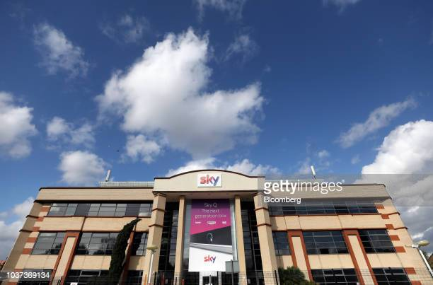 A visitor checks her mobile phone next to signage reading 'Welcome to Sky' outside the Sky Plc headquarters in Isleworth London UK on Friday Sept 21...